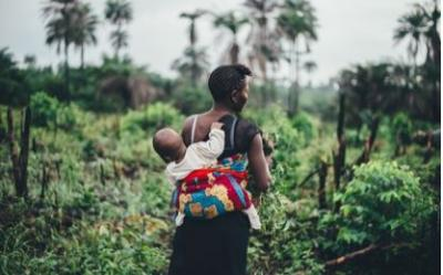 Woman in Africa carrying baby